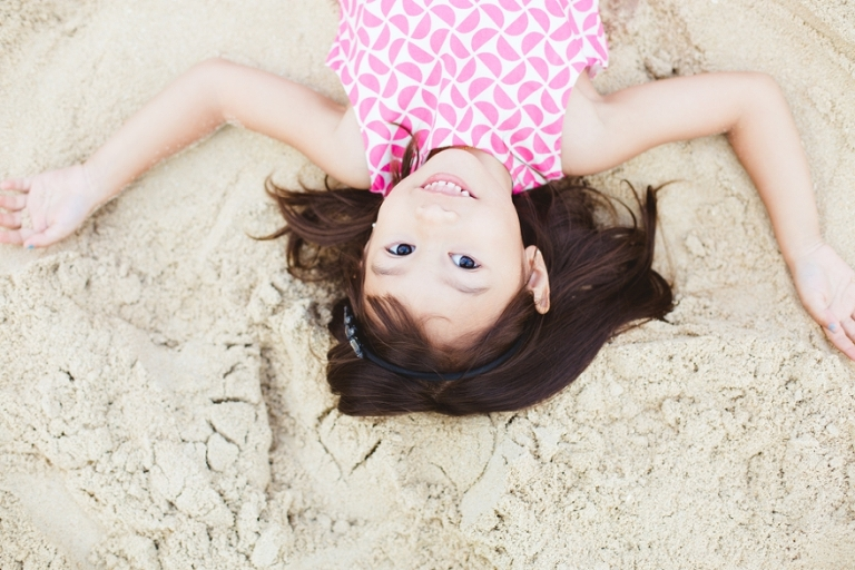 cute little girl laying on the sand